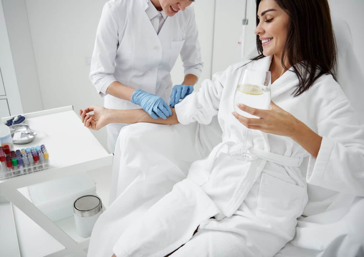Woman getting IV Therapy while relaxing and drinking lemon water