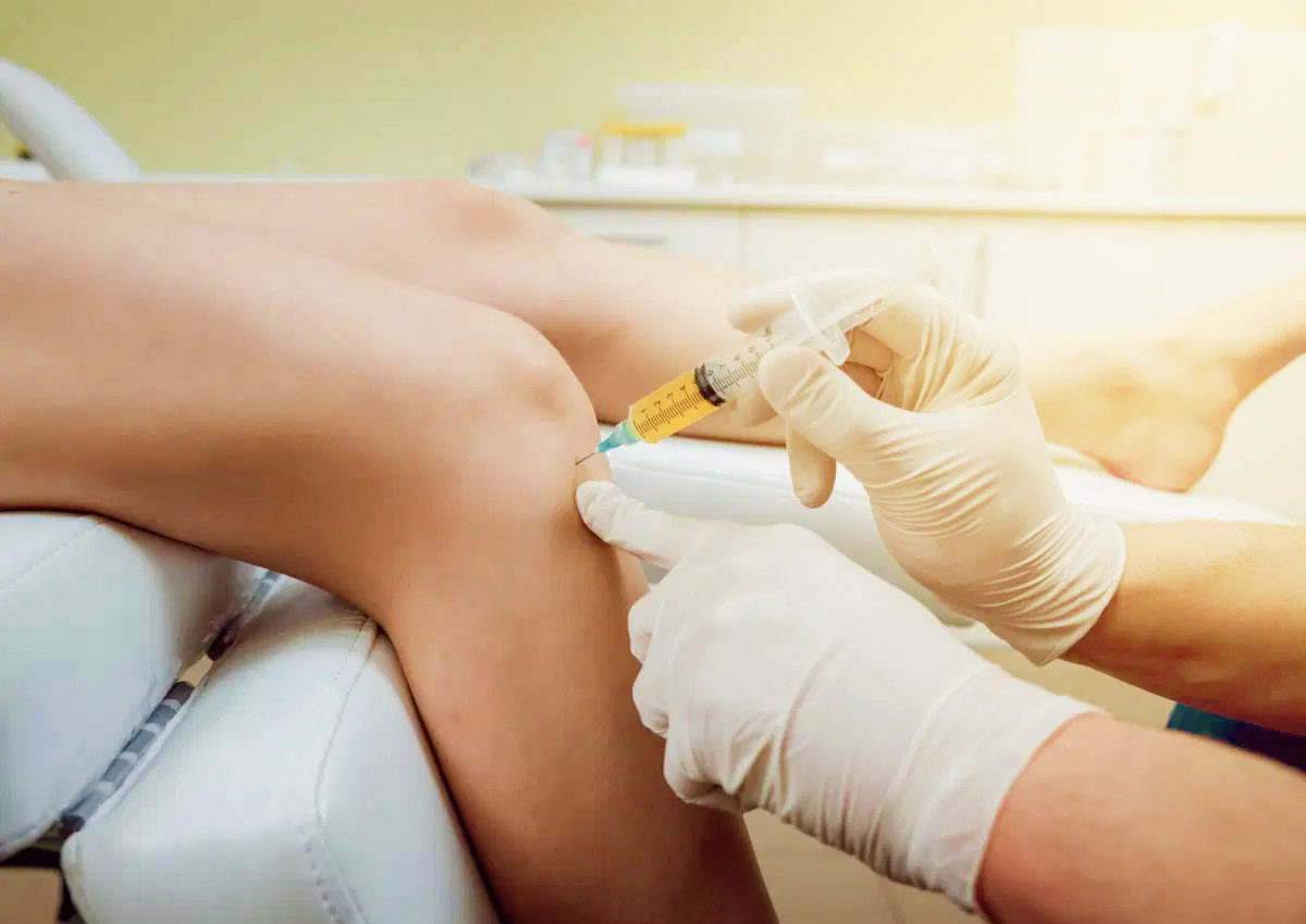 Doctor injecting PRP into a woman's knee