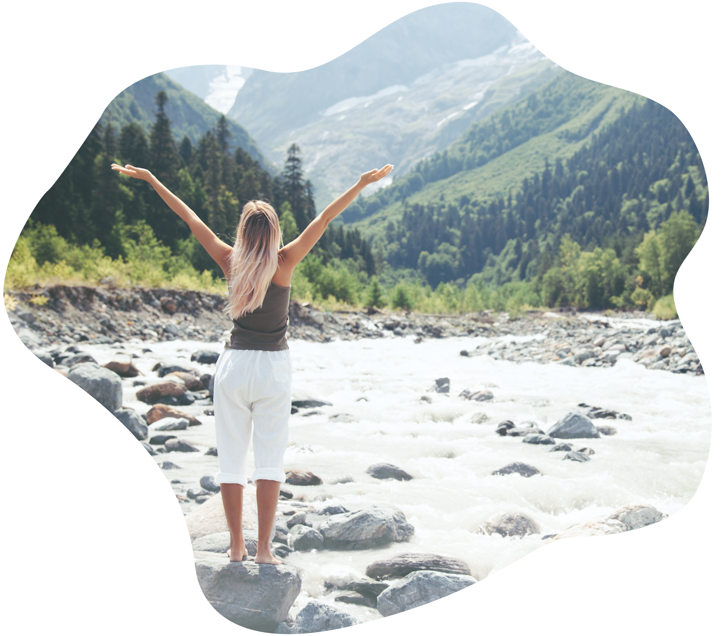 Woman with her arms out against a mountain and river landscape